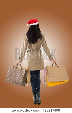 Christmas girl holding shopping bags, rear view portrait isolated.