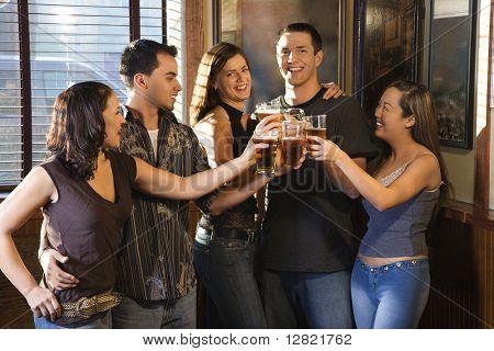 Gruppe junger Freunde hanging out in Kneipe und mit ihren Bieren Toasten.