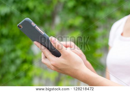 Young girl looks at mobile in the park