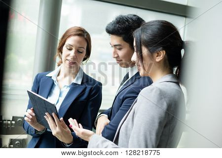 Business people discuss on digital tablet