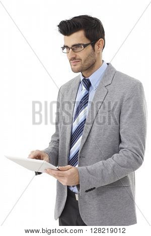 Young businessman using tablet computer, looking away, smiling.