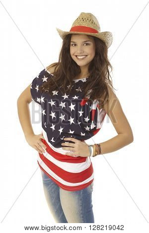 Portrait of happy American woman in American flag t-shirt and straw hat smiling with hand on hip.