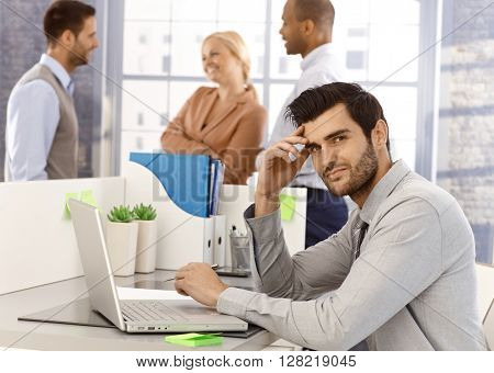 Portrait of young businessman sitting at desk, having laptop, working, looking at camera.