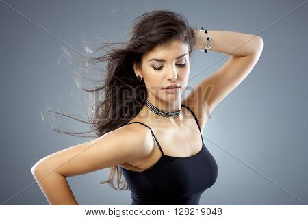 Beautiful sexy woman posing in top with long hair, hand in hair.