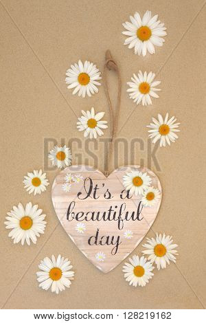 Its a beautiful day sign with daisy flowers on beach sand background.