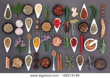 Large spice and herb food sampler forming an abstract background over grey.