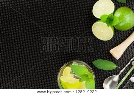 Mojito cocktail and ingredients over black rubber mat. Top view with copy space