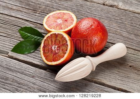 Fresh ripe red oranges and juicer on wooden table