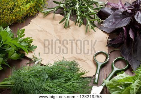 Fresh garden herbs and piece of paper for your recipes on wooden table. Top view with copy space