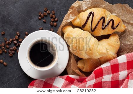 Fresh homemade croissants with chocolate and coffee on stone table. Top view