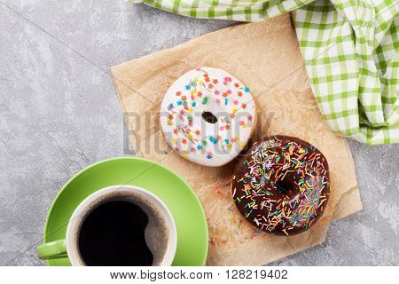 Colorful donuts and coffee on stone table. Top view with copy space