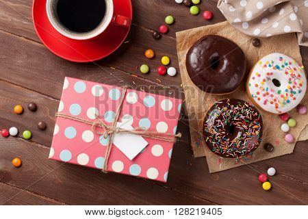 Donuts, gift box and coffee on wooden table. Top view