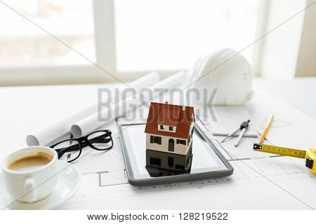 architecture, building, construction, real estate and home concept - close up of living house model on tablet pc computer screen