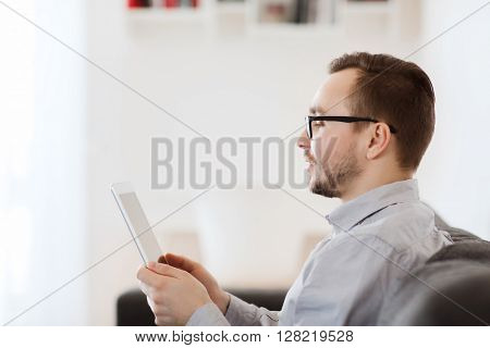 technology, people and distance learning concept - happy man working with tablet pc computer at home