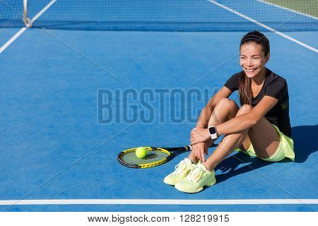Tennis player woman wearing sports smartwatch. Beautiful sport athlete portrait resting on blue outdoort hardcourt relaxing happy with wearable tech wristwatch for activity tracker on fitness workout.