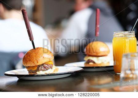 Cheeseburgers and lemonade in jar on table