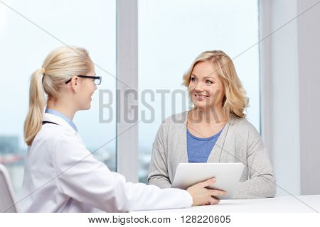 medicine, health care and people concept - smiling doctor with tablet pc computer and woman meeting at hospital