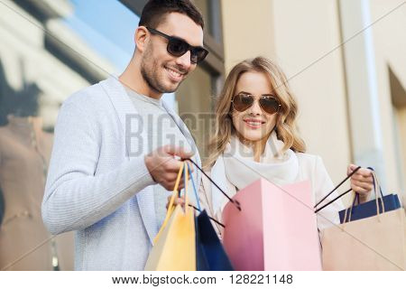 sale, consumerism and people concept - happy couple looking into shopping bag at shop window on city street