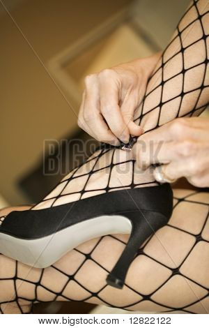 Close up of Caucasian woman in fishnet stockings putting on high heel shoes.