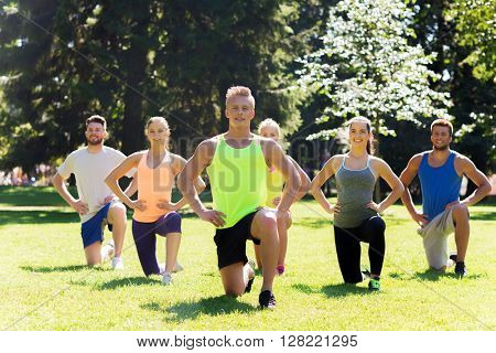 fitness, sport, friendship and healthy lifestyle concept - group of happy teenage friends or sportsmen exercising and stretching knee at boot camp