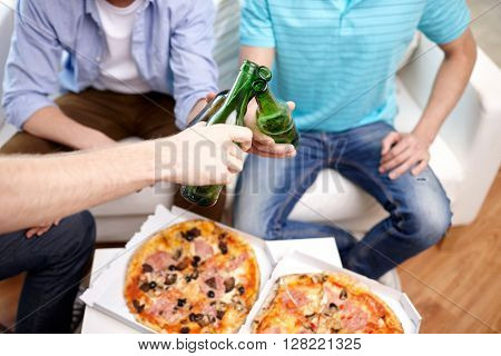 friendship, alcohol, people, celebration and holidays concept - close up of male hands clinking beer bottles and eating pizza at home