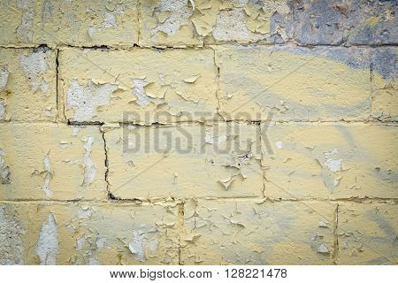 texture of old building wall with yellow, peelling off paint