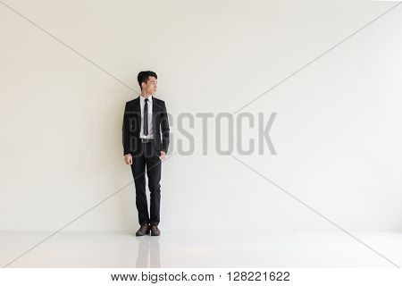 young asian businessman against the white wall