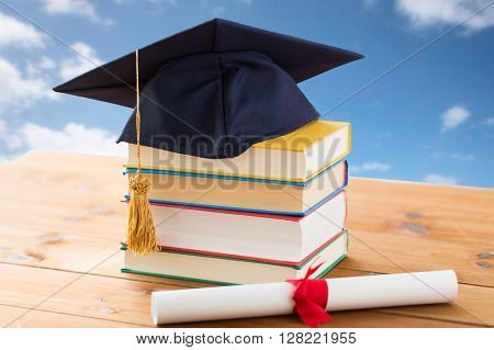 education, school, graduation and knowledge concept - close up of books and mortarboard with diploma on wooden table over blue sky and clouds background