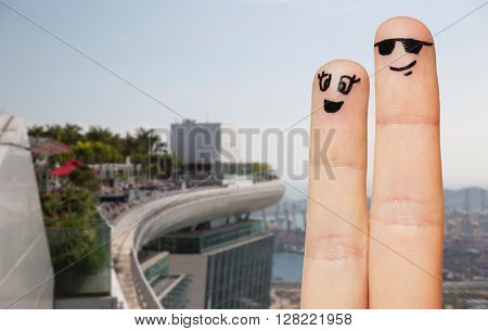 family, couple, travel, tourism and body parts concept - close up of two fingers with smiley faces over dubai city hotel background