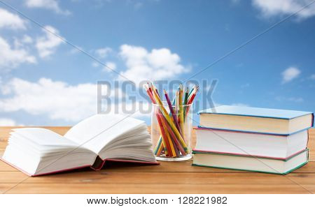 education, school, creativity and object concept - close up of crayons or color pencils and books on wooden table over blue sky and clouds background