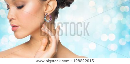 glamour, beauty, jewelry and luxury concept - close up of beautiful woman face with earring over blue holidays lights background