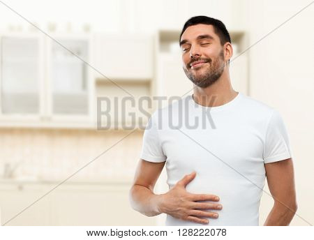 eating, satisfaction and people concept - happy full man touching his tummy over kitchen background