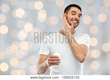 beauty, skin care, body care and people concept - smiling young man applying cream or lotion to face over holidays lights background