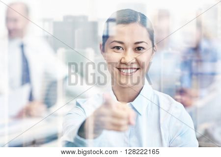 business, people and teamwork concept - smiling businesswoman pointing finger at you with group of businesspeople meeting in office