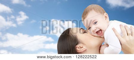 family, motherhood, parenthood, love and happy people concept - happy mother kissing her baby over blue sky and clouds background