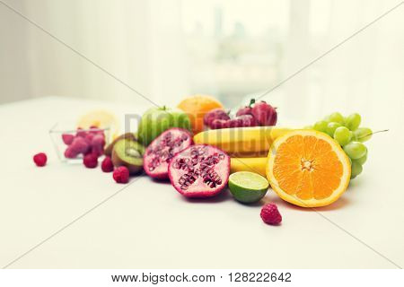 healthy eating, food and diet concept- close up of fresh ripe fruits and berries on table