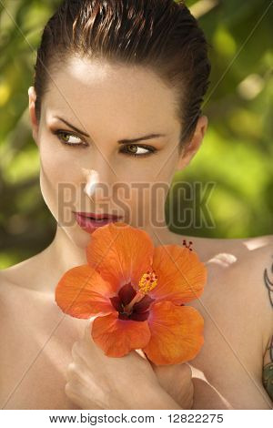 Attractive nude Caucasian tattooed woman holding Hibiscus flower in Maui, Hawaii, USA.