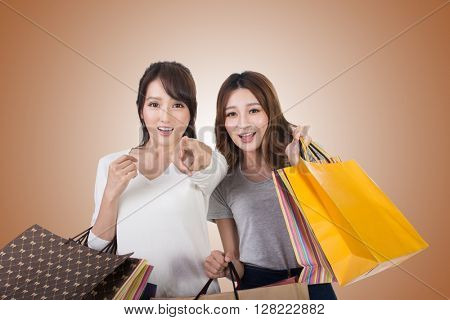 Asian shopping woman with her friends holding bags.