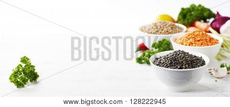 Bowls of assorted dried lentils with vegetables over white