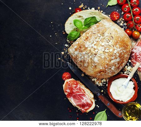 Homemade bread loaf and fresh ingredients for making sandwiches (tomatoes, basil, olive oil, cream cheese) on rustic dark background. Background layout with free text space.