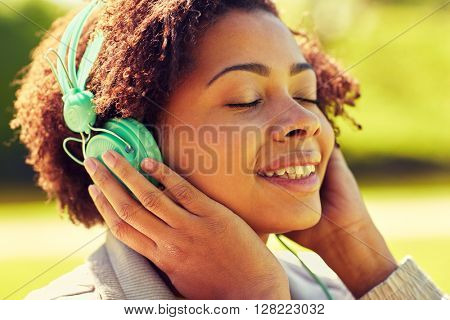 people, summer, technology and leisure concept - happy african american young woman face with headphones listening to music outdoors