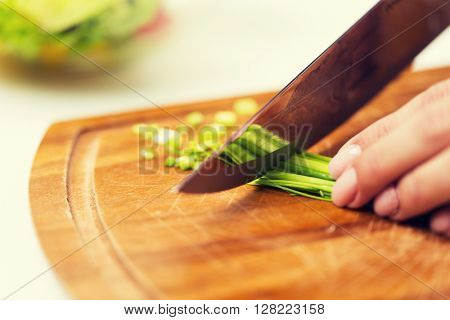 healthy eating, cooking, vegetarian food, dieting and people concept - close up of woman chopping green onion with knife on wooden cutting board