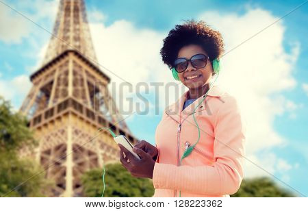 technology, travel, tourism and people concept - smiling african american young woman or teenage girl with smartphone and headphones listening to music over eiffel tower background