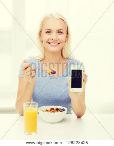 healthy eating, dieting and people concept - smiling young woman with tablet pc computer eating breakfast and showing blank smartphone screen at home