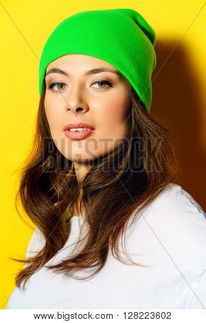Trendy girl wearing bright green hat standing by a yellow wall. Bright style, youth fashion.