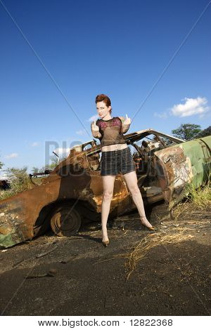 Sexy tattooed Caucasian woman standing giving middle finger in front of old rusted car in junkyard.