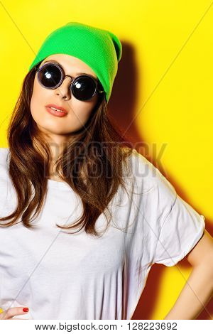 Trendy girl wearing sunglasses and bright green hat standing by a yellow wall. Bright style, youth fashion.