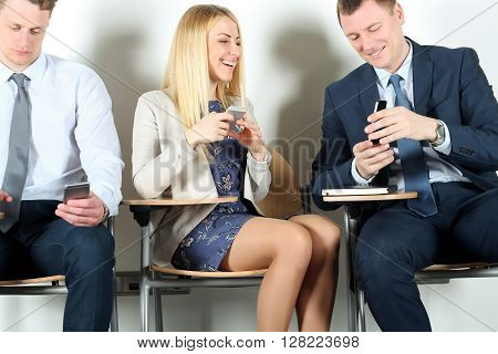 Business colleagues sitting on chairs and using mobile phone. Businesswoman laughing