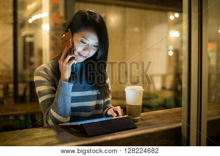 Woman talk to cellphone and use of tablet at coffee cup