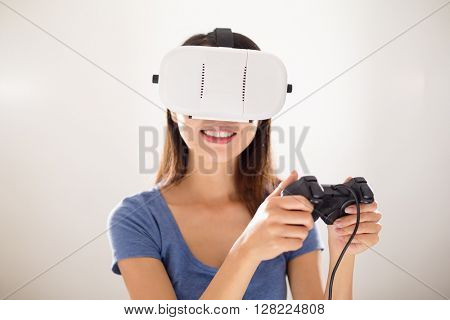 Woman wearing virtual reality and playing video game